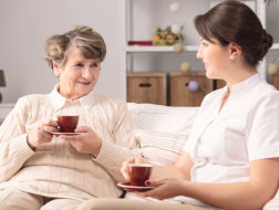 elderly woman and a caregiver having a cup of coffee