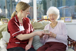 caregiver handed a cup of coffee to the elderly woman