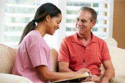 elderly man talking to a caregiver