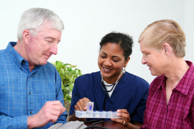 caregiver assisting the elderly couple on their medication