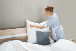 young woman cleaning the bedroom