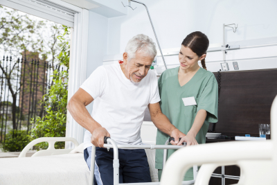 helping senior male patient in using walker